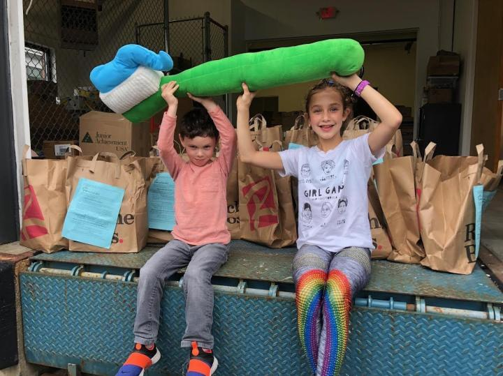 A young boy and girl sit on a loading dock holding Hope and Comfort's iconic stuffed toothbrush over their heads with donation bags filled with toiletries behind them.