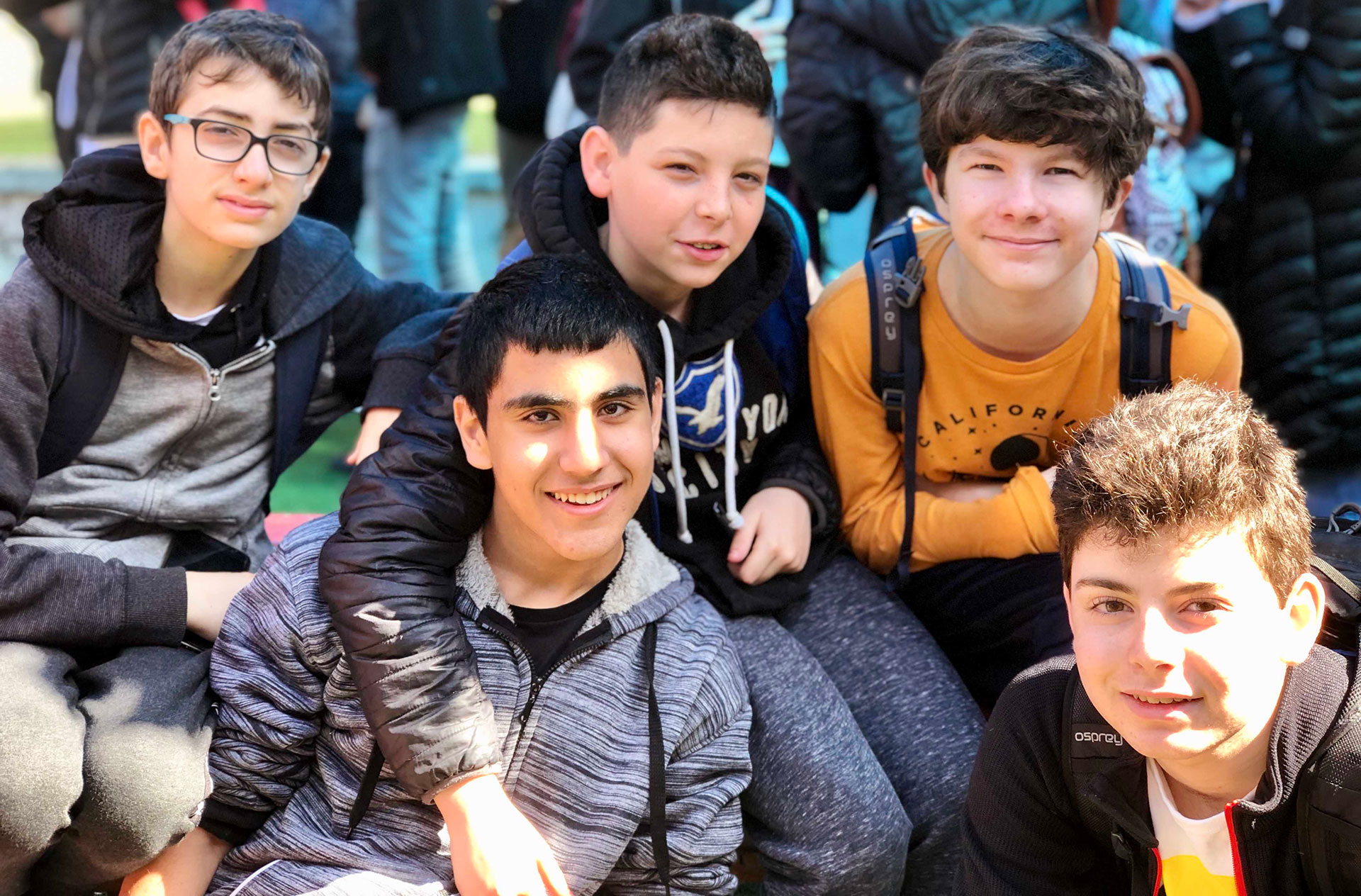A group of Israeli and American boys sit together outdoors.