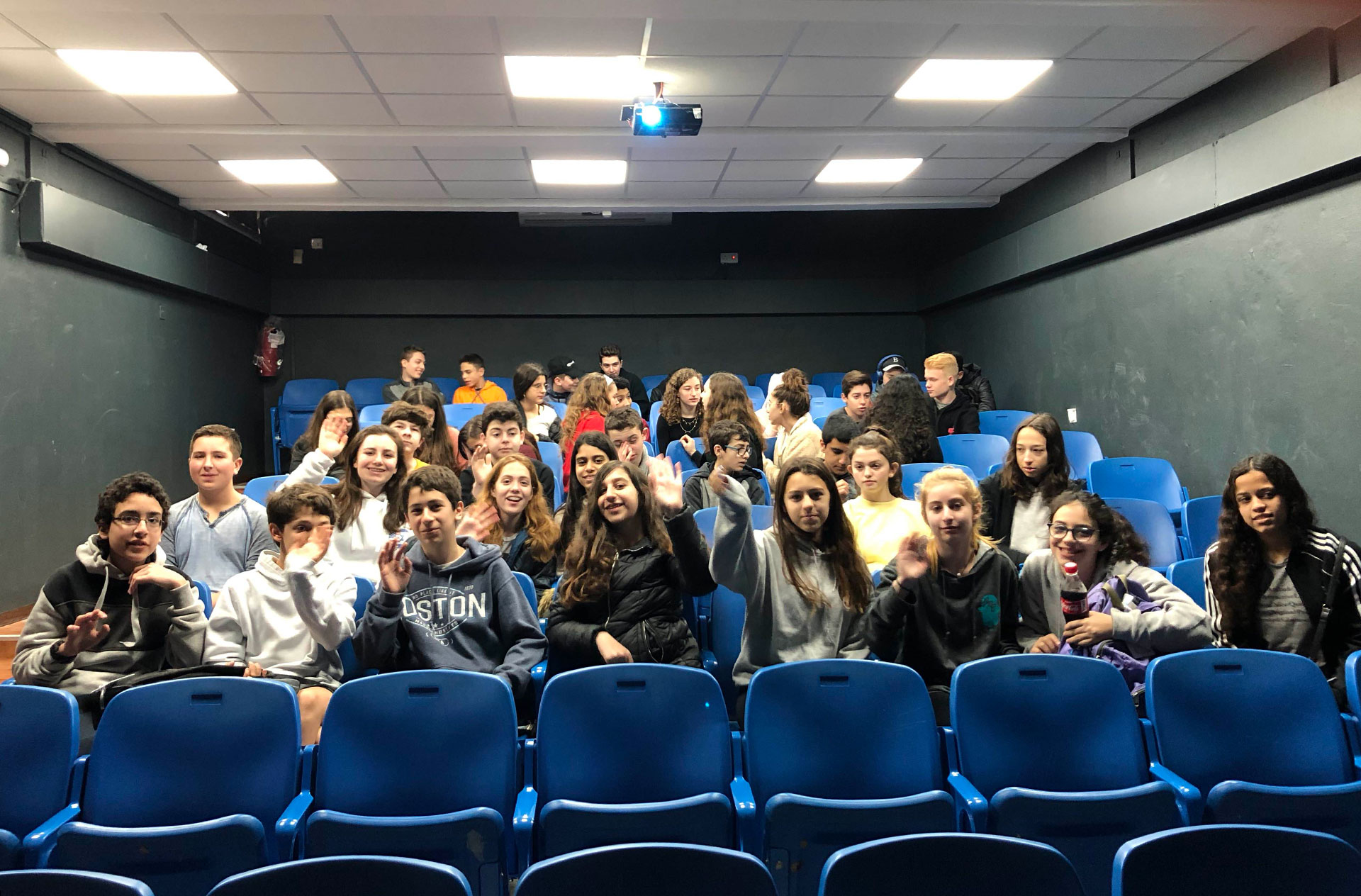 Students from The Rashi School and Leo Baeck pose for a photo while seated in an auditorium in Haifa.